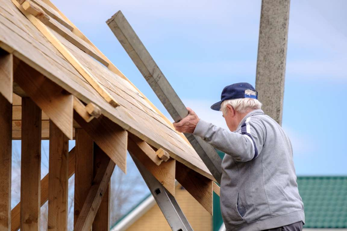 Senior gray-haired builder collects the frame of a wooden country house