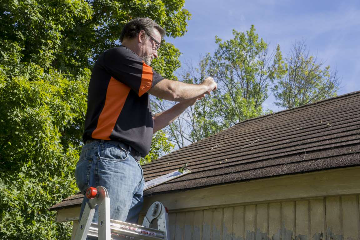 Contractor Taking Photos Of Hail Damaged Roof